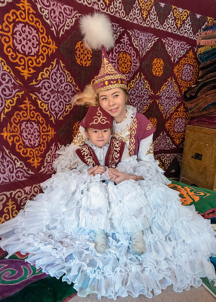 Kazakh mother and daughter in an intimate moment in a yurt, Almaty, Kazakhstan