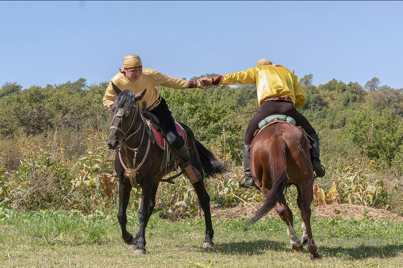 Two mounted Kazakh men horseback wrestling, Almaty, Kazakhstan