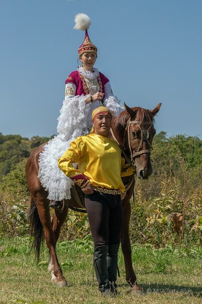 Kazakh couple in traditional attire with their horse, Almaty, Kazakhstan