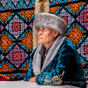 Portrait of a Kazakh man in traditional attire, with fox skin on wall of yurt, Almaty, Kazakhstan