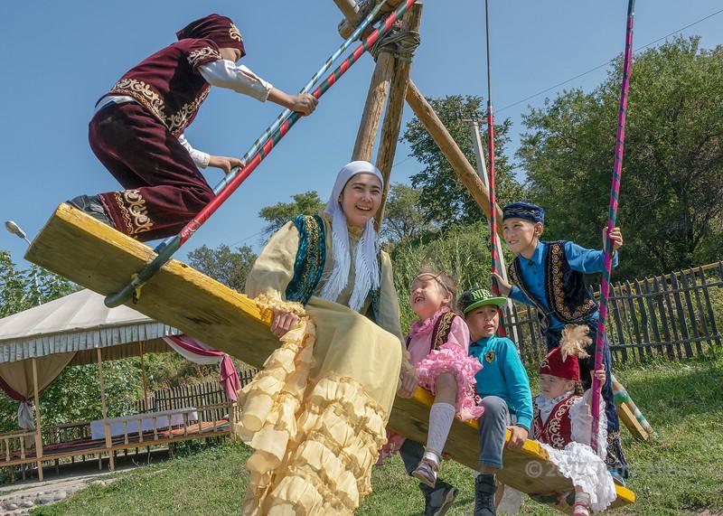 Fun on a swing, young Kazakhs in festive attire, Almaty, Kazakhstan