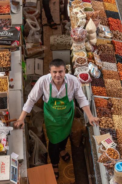 Man in green apron selling dried fruit and nuts, Green (Zelyony) Bazaar, Almaty, Kazakhstan