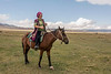 Woman herder riding across the high steppes of Assy Plateau, Kazakhstan