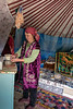 Kazakh woman preparing to make tea inside a yurt, Assy Plateau, Kazakhstan