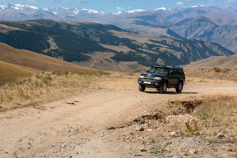 Touring along the dirt roads of the high Assy Plateau with a view of the Tian Shan mountains, Kazakhstan