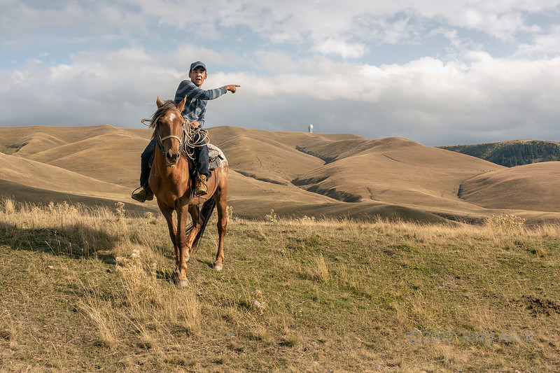 Kazakh horseman pointing out the Assy Turgen Obervatory, Assy Plateau, Kazakhstan