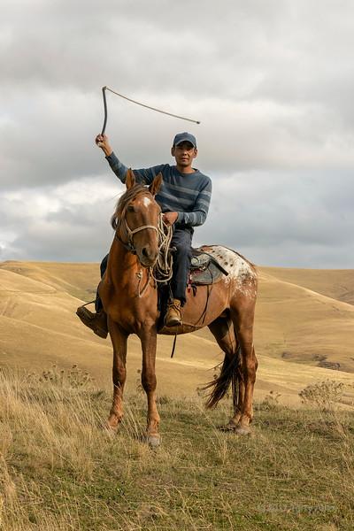 Kazakh horseman swinging his whip, Assy Plateau, Kazakhstan