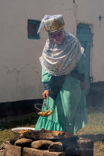 Kazakh elder enveloped in smoke as she fried baursak over an open fire, Sharahkent, Kazakhstan