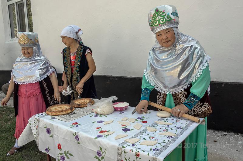 Kazakh elder in traditional attire cutting dough for baursak, Sharafkent, Kazakhstan