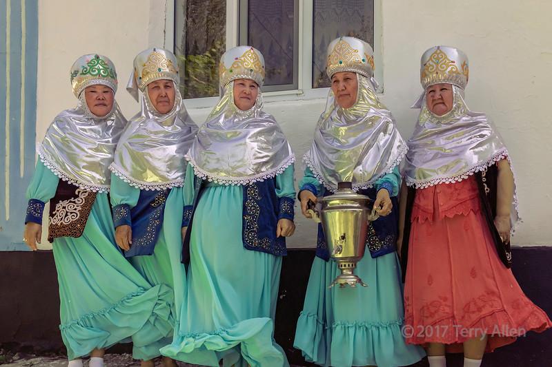 Kazakh village grandmothers holding samovar on a windy day, Sharafkent, Kazakhstan