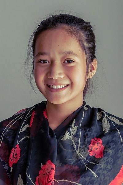 Portrait of a smililng Kazakh girl lit by a window, Sharafkent, Kazakhstan sm