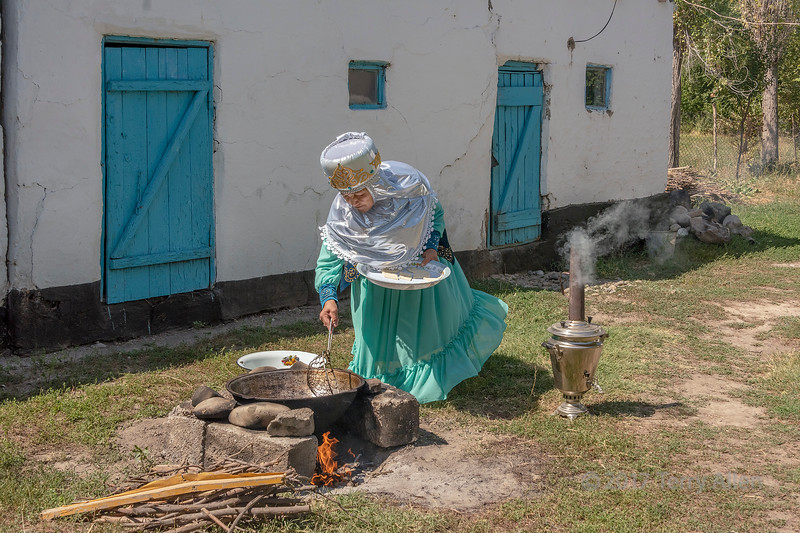 Village elder making baursak over an open fire, Sharafkent, Kazakhstan