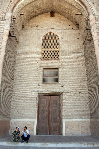 Main portal of the mausoleum of Khoja Ahmed Yasawi with couple squtting on the steps, Turkestan, Kazakhstan