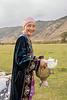 Kazakh woman carrying tube samovar and teapot at a yurt raising ceremony, Saty, Kazakhstan