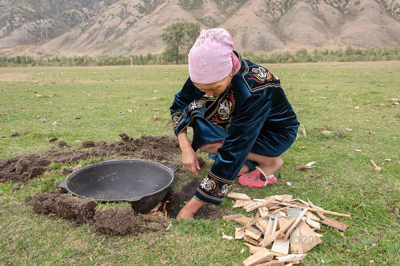 Woman lighting a fire under the wok to fry baursaki (Kazak fried dough), Saty, Kazakhstan