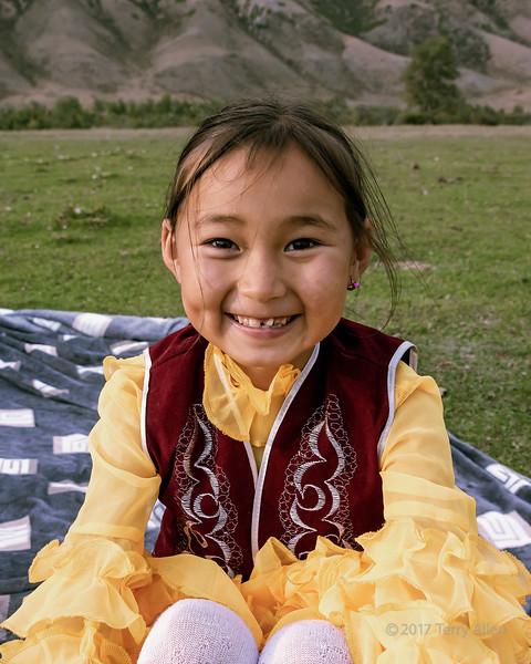 Kazakh girl sitting on a blanket, Saty, Tian Shan Mountians, Kazakhstan