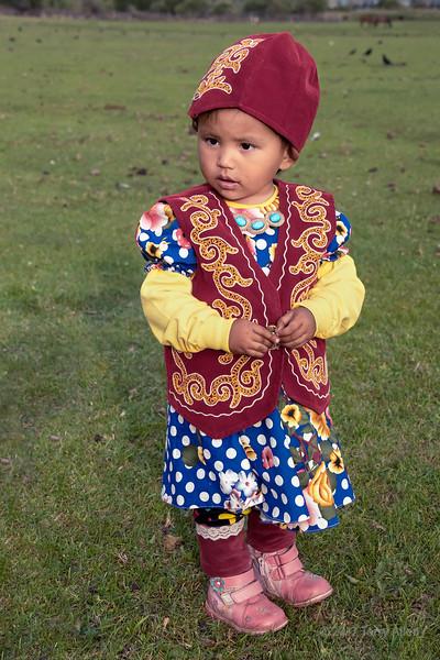 Portrait of a small Kazakh girl at a yurt raising, Saty, Tian Shan Mountains, Kazakhstan