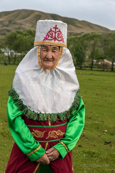 Kazakh grandmother in traditional attire at yurt raising, Saty, Kazakhstan