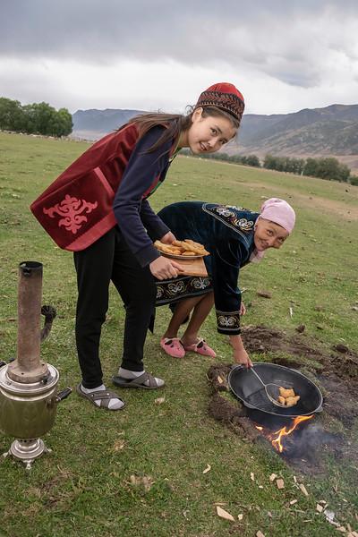 Kazakh women frying baursaki in a wok over an open flame, Saty, Kazakhstan