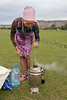 Woman stirring the coals in a samovar with a stick, Saty, Kazakhstan