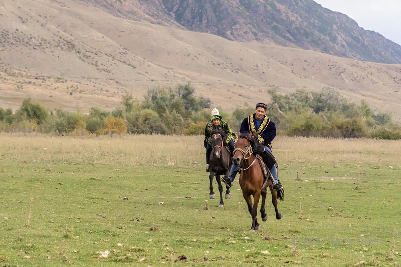Pair of Kazakh youth racing their horses across a grassy plain, Saty, Kazakhstan