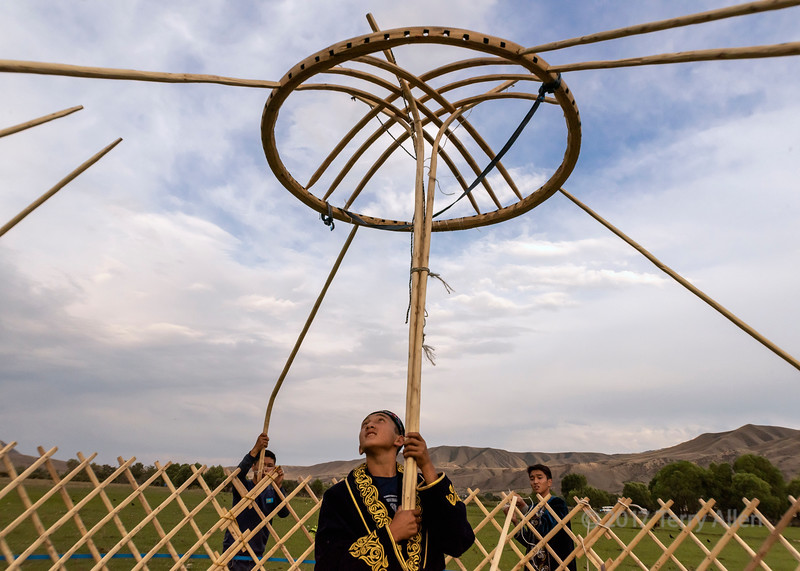 Fitting the bent roof poles into the holes on the rim of the shangyrak (wooden crown), yurt raising, Saty, Tian Shan Mountains, Kazakhstan