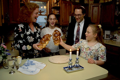 Family Welcomes Shabbat by Singing, Lighting Candles, and Blessing Challah
