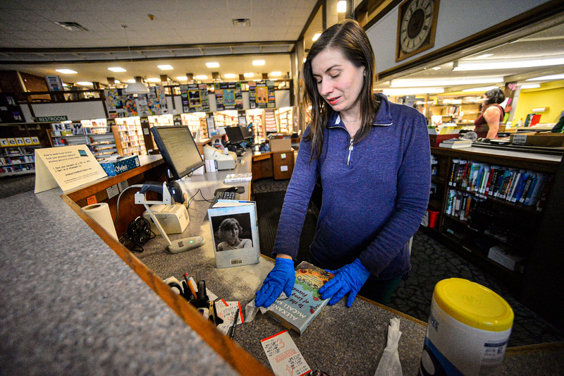 KRISTOPHER RADDER — BRATTLEBORO REFORMER<br /> Klara Charlton, circulation department at Brooks Memorial Library, in Brattleboro, Vt., uses Clorox wipes to keep the books clean from COVID-19 on Tuesday, March 17, 2020.