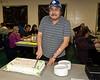 Ken Wesley cutting cake.