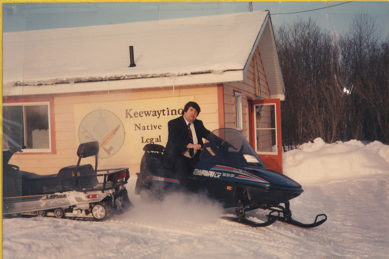 """Crop showing Paul Lantz driving snowmobile -- Interior of """"the Northern Lawyer"""" file folder. Includes seven photographs and two captions. Four photographs show Paul Lantz on clinic snowmobile, one shows Laura Howarth standing outside by a snowmobile, one shows Paul Lantz at his desk and the seventh shows Laura Howarth standing in library doorway. Early 1990s, photographs taped to folder."""