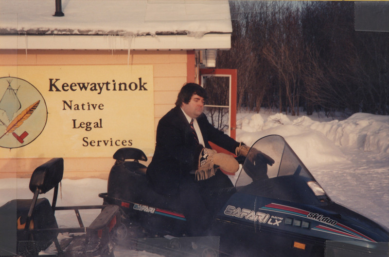 """Crop showing Paul Lantz in suit on clinic snowmobile by sign. -Interior of """"the Northern Lawyer"""" file folder. Includes seven photographs and two captions. Four photographs show Paul Lantz on clinic snowmobile, one shows Laura Howarth standing outside by a snowmobile, one shows Paul Lantz at his desk and the seventh shows Laura Howarth standing in library doorway. Early 1990s, photographs taped to folder."""