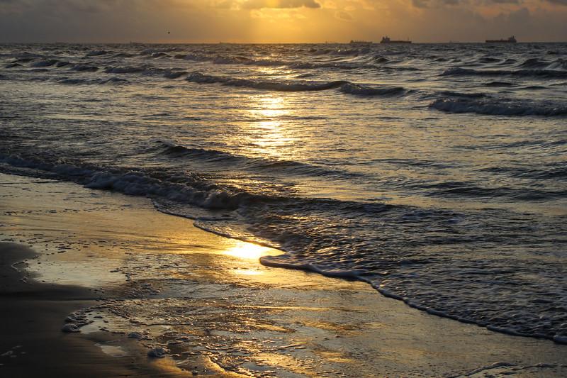 Golden sunrise reflecting on the beach