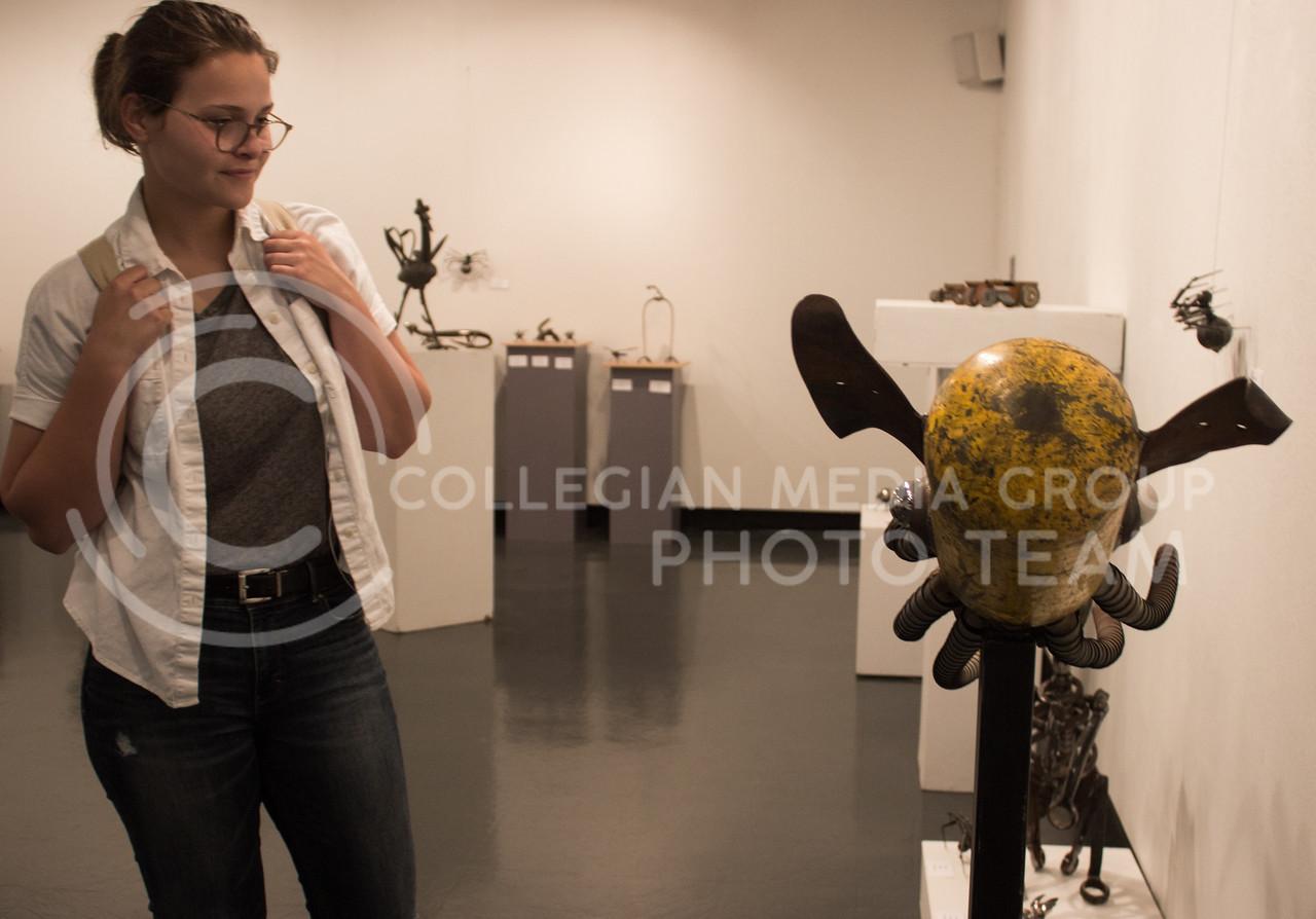 "Hannah Burtz, freshman in business administration, looks at ""El Calamari"" an art piece by Larry Goodwin on display in the William T. Kemper Art Gallery on August 31, 2017. (Regan Tokos | Collegian Media Group)"