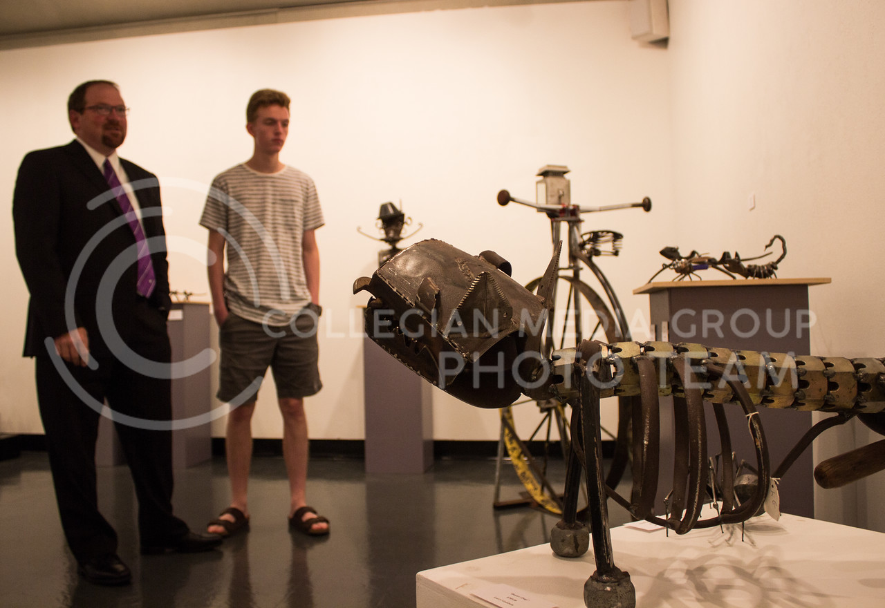 Zac Caffey, freshman in engineering, and his father, Rob Caffey, Vice Provost in Information and Technology Services, look at the exibit of Lary Goodwin's sculputure work on display in the William T. Kemper Foundation Art Gallery together over their lunch break on August 31, 2017. (Regan Tokos | Collegian Media Group)