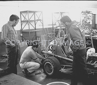 Houston, Foyt works on Midget as George Snider in  jacket and crew man look on, 1970