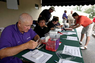 Doug Kingsley sorts entry forms and raffle tickets Friday afternoon during the Golf Scramble at Owensboro Country Club. The scramble was part of the Kentucky Wesleyan College Basketball 100th Anniversary celebration.