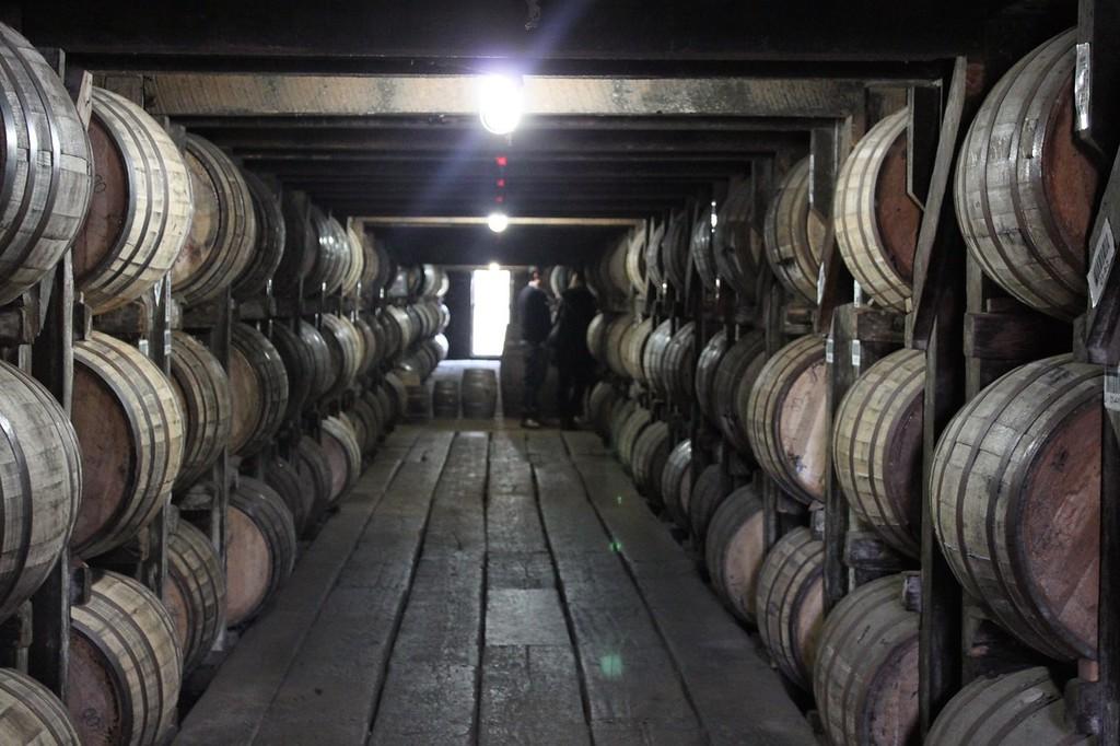 A dark room has rows upon rows of barrels of aging bourbon