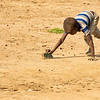 Maasai boy using a rock as his toy car