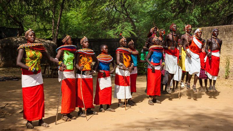 Africa. Kenya. Young Samburu morani dance with women in colorful, traditional dress at a ceremony at Samburu NP.