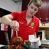 Roger Schneider | The Goshen News<br /> Mollie Kieffer makes a carmel apple Saturday at Kercher's Orchard and Farm Market's Fall Harvest Festival Saturday.