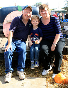 Roger Schneider | The Goshen News Dave and Elaine Lange of Mishawaka and their grandson Colin Amstutz, 4, Mishawaka sit in the back of a farm truck for a family photo Saturday during Kercher's Sunrise Orchard and Farm Market's Fall Harvest Festival.