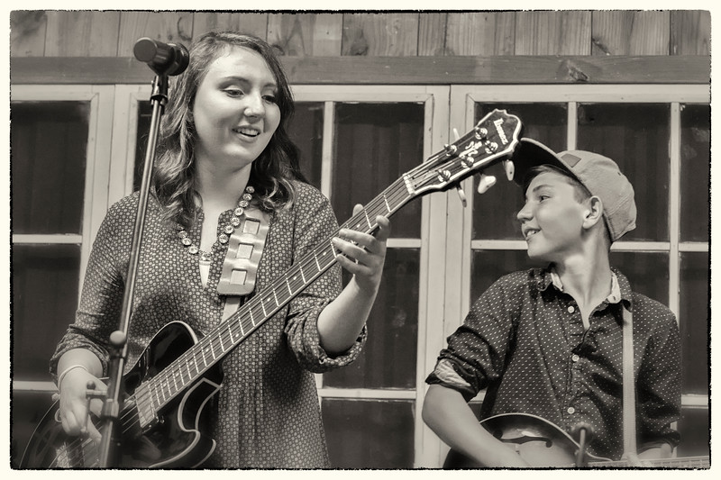 Liza feels the notes out on her guitar as little brother, Asa, on mandolin, looks on
