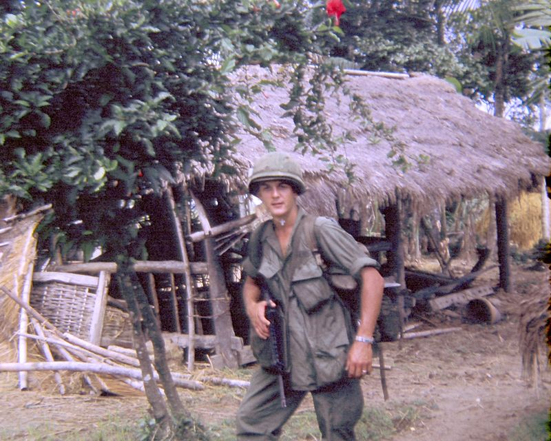 EK-25 Emil Ketelhut, Jr. (MI) of 2nd Platoon at a straw hooch in the 'Nam with his M-16.