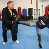 Xzaveir Jean, 8, a student at Kevin Bliss Self Defense Center in Leominster showed off some defensive kicks he has learned. This one is the side kick. Kevin Bliss holds a bag for him to kick during the class. SENTINEL & ENTERPRISE/JOHN LOVE