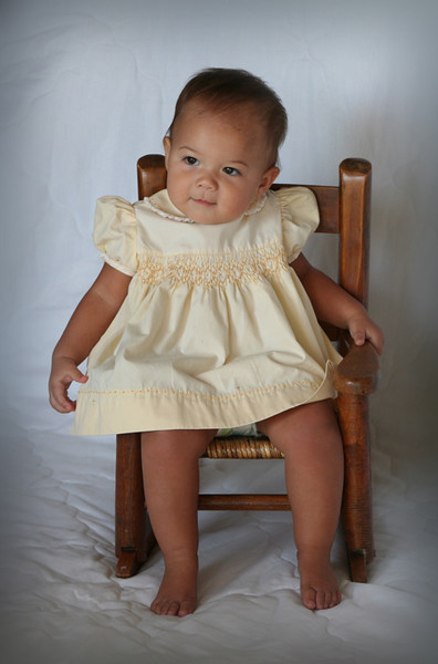 LILLYONNA IS IN A DRESS THAT HER GREAT, GREAT MAMMAW MADE FOR HER GRANDMA SIBERT WHEN SHE WAS A LITTLE GIRL.  SHE IS ROCKING IN HER GREAT GRANDPAS CHAIR FROM WHEN HE WAS A LITTLE BOY.