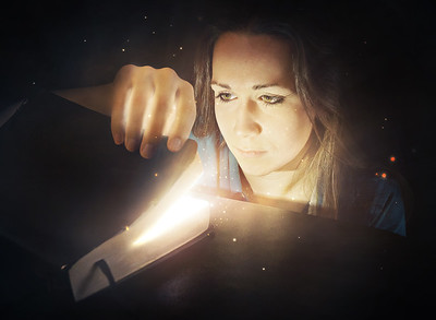 Woman looking into glowing Bible.