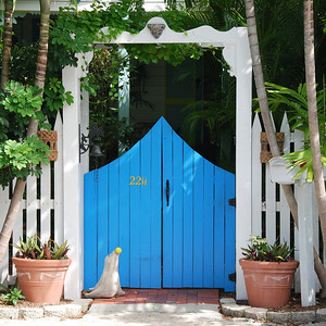 This pretty entrance with a blue gate has a sealion for a guard.