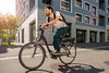 Mit dem Velo unterwegs – ein Bewohner des Hunziker-Areals; Un habitant du site Hunziker à vélo; Un abitante in bici nell'area di Hunziker