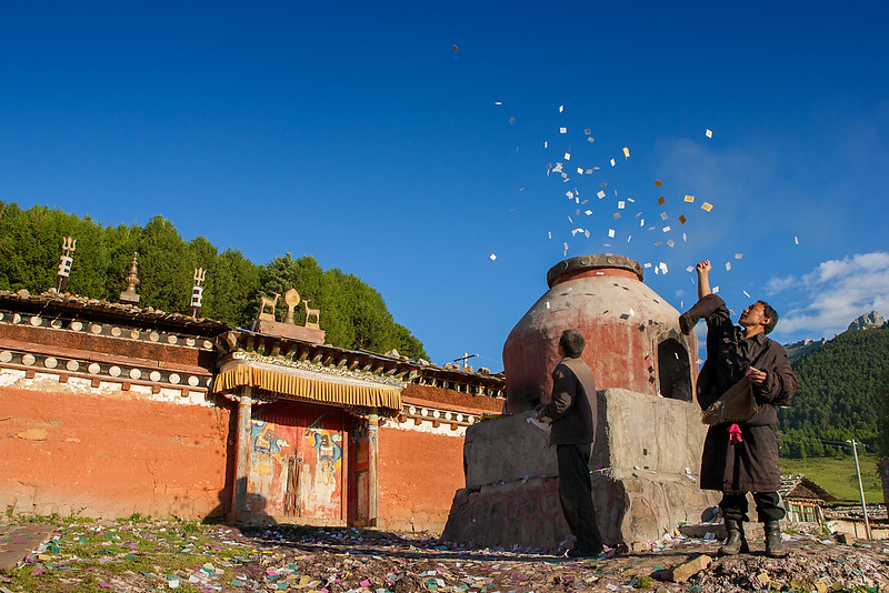 A man throwing paper Wind Horses to the sky. Taktsang Lhamo (Langmusi), Amdo (Gansu)