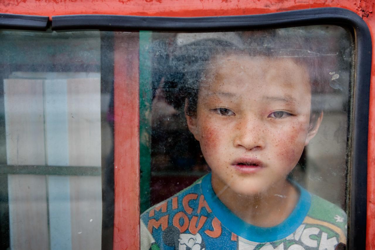 Young boy in shop window. Near Drakar Tredzong Monastery, Xinghai, Amdo (Qinghai)